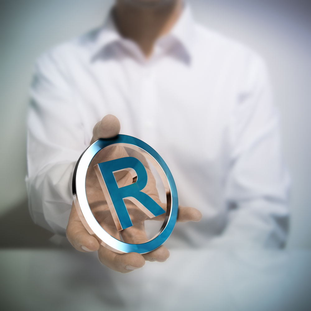 Man holding metallic registered trademark symbol. Concept image for illustration of intellectual property or protection of products or services.